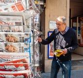 Senior man buying newspaper reporting handover ceremony presiden. PARIS, FRANCE - MAY 15, 2017: Senior man buys international newspaper reporting handover Stock Image