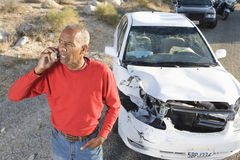 Senior Man On Call With Damaged Car In The Background Royalty Free Stock Photography