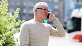 Senior man calling on smartphone in city stock footage