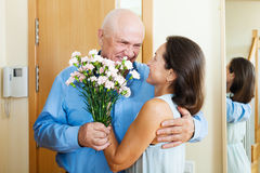 Senior man came to mature woman with flowers Royalty Free Stock Photography