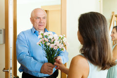 Senior man came to mature woman with flowers Stock Photo