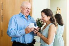 Senior man came to mature woman with present Stock Images