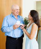 Senior man came to  woman with gift Royalty Free Stock Photos
