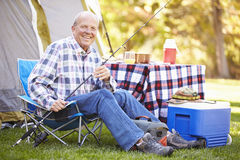 Senior Man On Camping Holiday With Fishing Rod. Smiling To camera royalty free stock photography