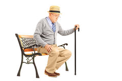Senior man with a cane sitting on a bench Royalty Free Stock Images