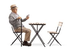 Senior man with a cane sitting at a table and playing cards stock image