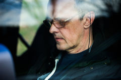 Senior man in car read text on smartphone Stock Photography