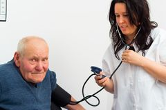 Senior Man At The Cardiology. Elderly patient at the cardiology - doctor measuring his blood-pressure Royalty Free Stock Photography