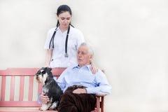 Senior man with caregiver and dog Royalty Free Stock Image