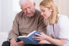 Senior man and caregiver. Senior men and caregiver reading interesting book Royalty Free Stock Photography
