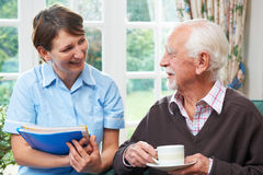 Senior Man With Carer At Home Stock Photo