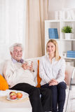 Senior man and carer. Senior men and carer sitting on the couch stock image