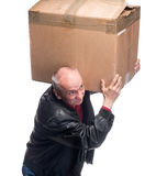 Senior man carries a heavy box. On a white background Stock Photos