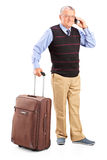 Senior man carrying a bag and talking on phone Royalty Free Stock Images
