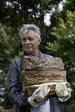 Senior man carrying firewood Royalty Free Stock Photos