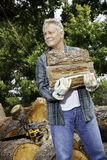 Senior man carrying firewood logs Royalty Free Stock Photos