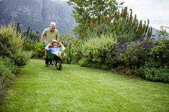 Senior man carrying his partner in wheelbarrow Stock Photography