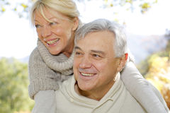 Senior man carrying his wife around on his back Royalty Free Stock Image