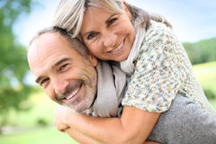Senior man carrying his wife on back Royalty Free Stock Photos