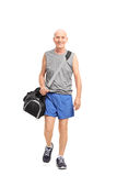 Senior man carrying a sports bag and walking Stock Photography