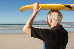 Senior man carrying surfboard on head at beach Royalty Free Stock Images
