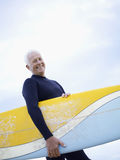 Senior Man Carrying Surfboard. Portrait of senior man carrying surfboard against sky Royalty Free Stock Photos