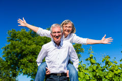 Senior man carrying woman piggyback Royalty Free Stock Photos
