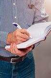 Senior man in casual cloth writing on a diary. Closeup Royalty Free Stock Photo