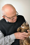 Senior man with a cat. Senior man wearing glasses with a cat royalty free stock photos