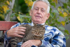 Senior man with cat in courtyard. Senior man hugging and cuddling his tabby cat on bench in courtyard stock photography