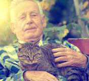 Senior man with cat in courtyard. Senior man hugging and cuddling his tabby cat on bench in courtyard Stock Photos