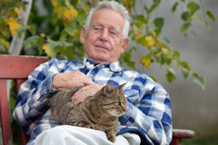 Senior man with cat in courtyard. Senior man hugging and cuddling his tabby cat on bench in courtyard Stock Images