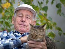 Senior man with cat in courtyard. Portrait of senior man in courtyard cuddling his tabby cat Stock Photography