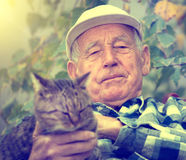 Senior man with cat in courtyard. Portrait of senior man in courtyard cuddling his tabby cat Stock Image