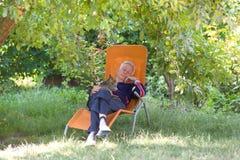 Senior man with cat in garden. Senior man taking nap at sunbed in shade in garden with cat in his lap royalty free stock photos