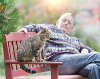 Senior man with cat. Senior man with his cat sitting on bench in the park Royalty Free Stock Photos