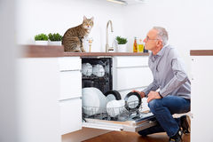 Senior man with cat in the kitchen. Empty out the dishwasher Royalty Free Stock Photos