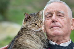 Senior man with cat. Portrait of old man with his tabby cat on his chest Royalty Free Stock Photo