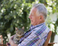 Senior man with cat. Senior man with tabby cat in his garden stock image