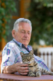 Senior man with cat. Senior man with tabby cat in his garden stock photo