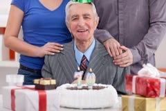 Senior man celebrating birthday with family. Happy senior man celebrating his 70th birthday with family Royalty Free Stock Images