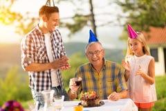 Senior man celebrating birthday with family. Happy senior men celebrating his birthday with family Royalty Free Stock Photo