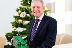 Senior man celebrating Christmas with present Stock Photography