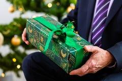 Senior man celebrating Christmas with present Stock Images