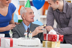 Senior man celebrating his birthday with family. Senior men celebrating his birthday with family and cake with  candles Royalty Free Stock Photos