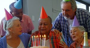 Senior man celebrating his birthday with friends 4k stock video