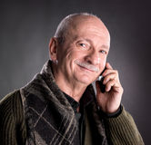 Senior man with cell phone. On a dark background Stock Photography