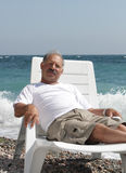 Senior man in the chaise lounge. Senior man resting in the chaise lounge on the beach stock photography