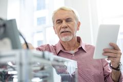 Senior man changing configurations of 3D printer according to instruction. Vital changes. Charming senior office worker changing configurations of 3D printer stock photo