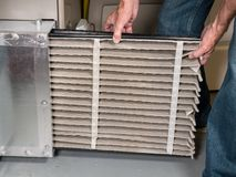 Senior man changing a dirty air filter in a HVAC Furnace. Senior caucasian man changing a folded dirty air filter in the HVAC furnace system in basement of home stock images